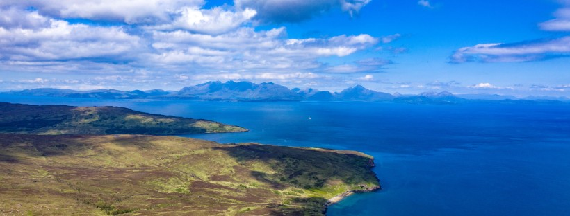 The Isle of Rùm's coastal hiking trail, with Skye's Cuillins looming in the background.